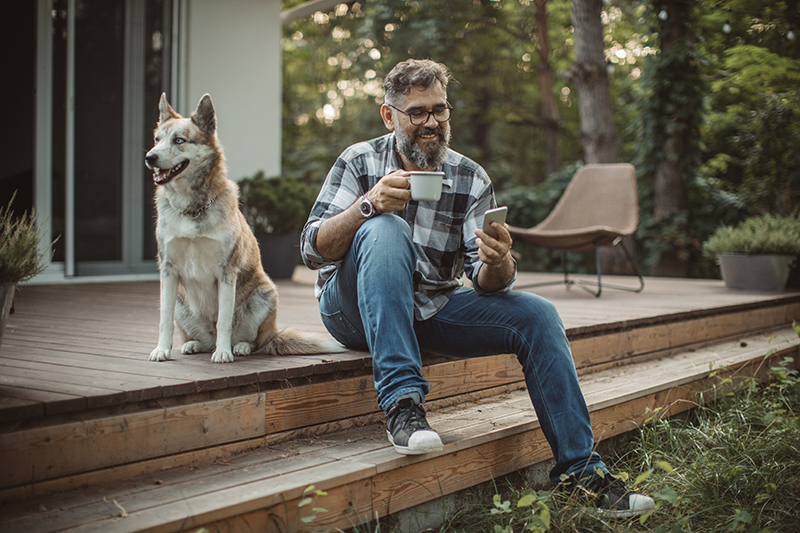 Mature men at his cottage resting on pprch with his dog. Sitting in cahair, drinking coffee and using smart phone. Wearing casual clothing.